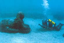 Diver examining submerged Sphinx off the coast of Alexandria, Egypt
